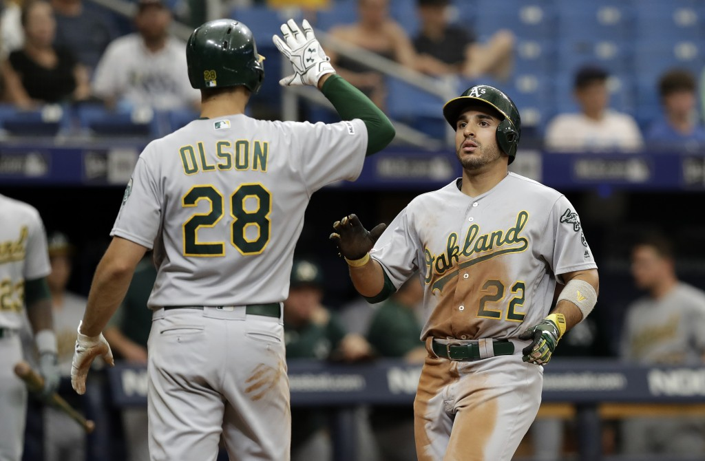 Oakland Athletics' Ramon Laureano (22) celebrates his grand slam off Tampa Bay Rays pitcher Colin Poche with Matt Olson (28) during the eighth inning