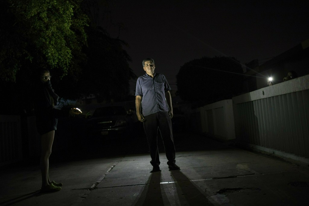 In this May 23, 2019 photo, Wilfido Briñez poses for photo while being illuminated by her daughter's cell phone, during a black out in Maracaibo, Vene