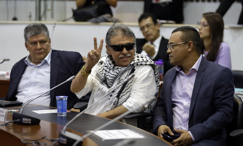 Former FARC rebel Jesus Santrich gives a victory signal to journalists as he attends a session of the Chamber of Representatives at the Colombian cong...