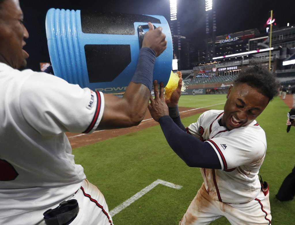 Atlanta Braves' Ozzie Albies, right, is doused by Ronald Acuna Jr., after driving in the winning run with a double in the 11th inning of a baseball ga...