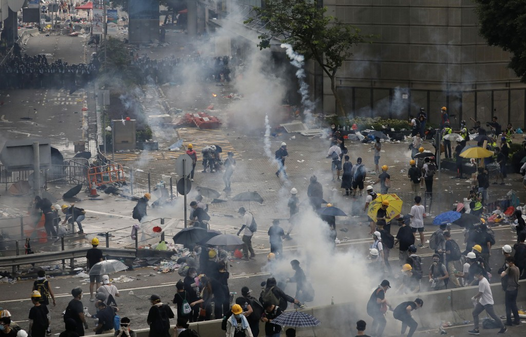 FILE - In this file photo taken Wednesday, June 12, 2019, riot police try to disperse protesters with fire tear gas outside the Legislative Council in...