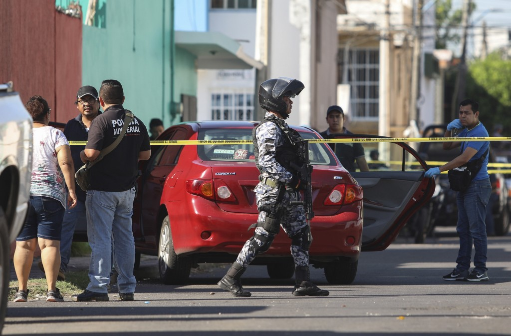 Police and forensic personnel work the crime scene where journalist Marcos Miranda was kidnapped, in Boca del Rio, Veracruz state, Mexico, Wednesday,