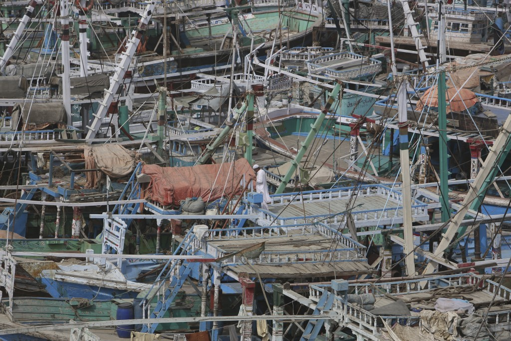 A fisherman stands on his boat as authorities call back fishing boats from the sea following a warning of Cyclone Vayu at Karachi harbor in Pakistan,