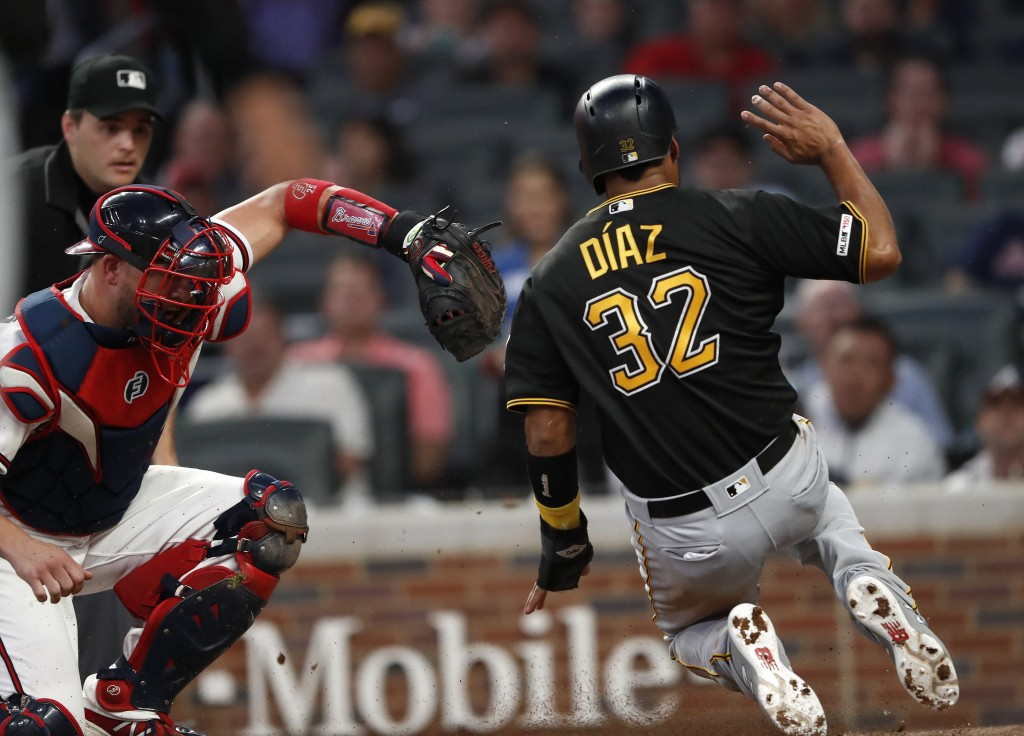 Pittsburgh Pirates' Elias Diaz (32) beats the tag from Atlanta Braves catcher Tyler Flowers to score on a Kevin Newman two-run double during the fourt...