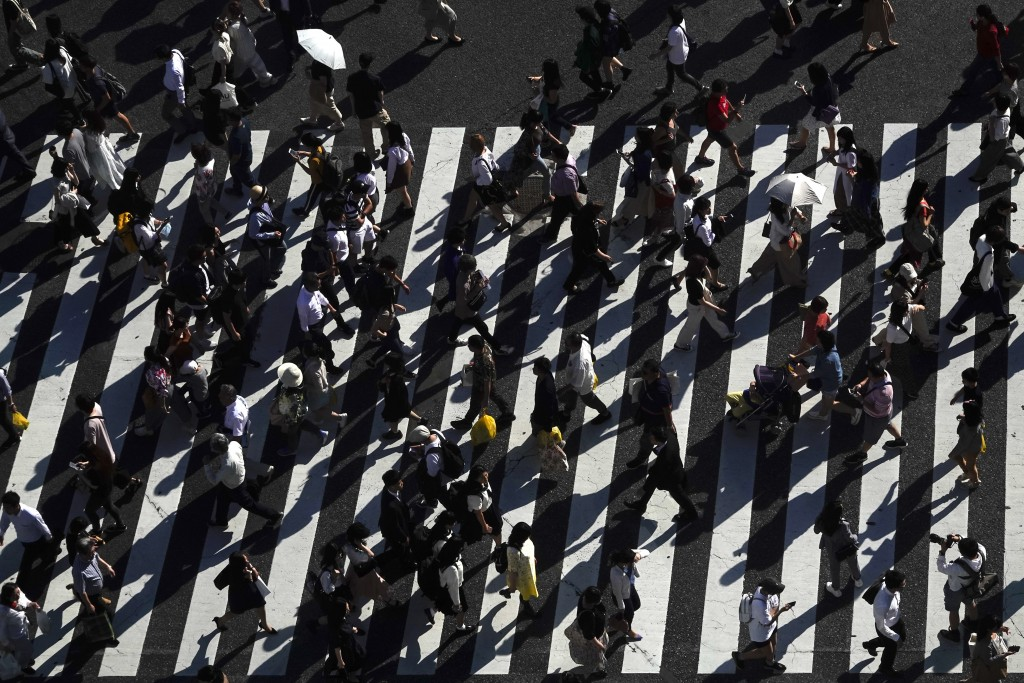 Pedestrians cast shadows as they walk across the famous Shibuya crossing Thursday, June 13, 2019, in Tokyo. It's not just a crossing. Located just out