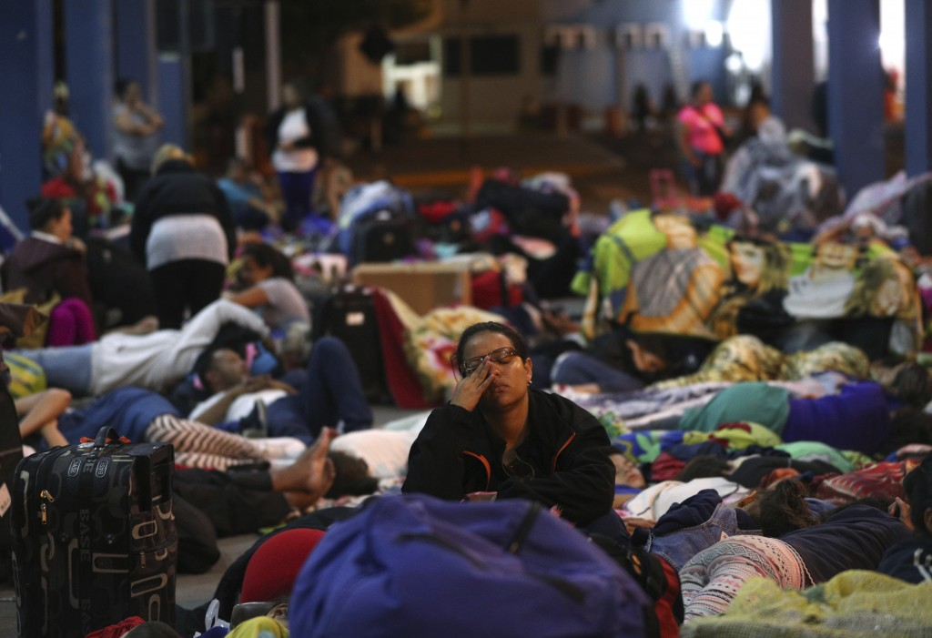 A Venezuelan migrants migrants rest near the border checkpoint as they wait to pass migration controls before the deadline on new regulations, in Tumb