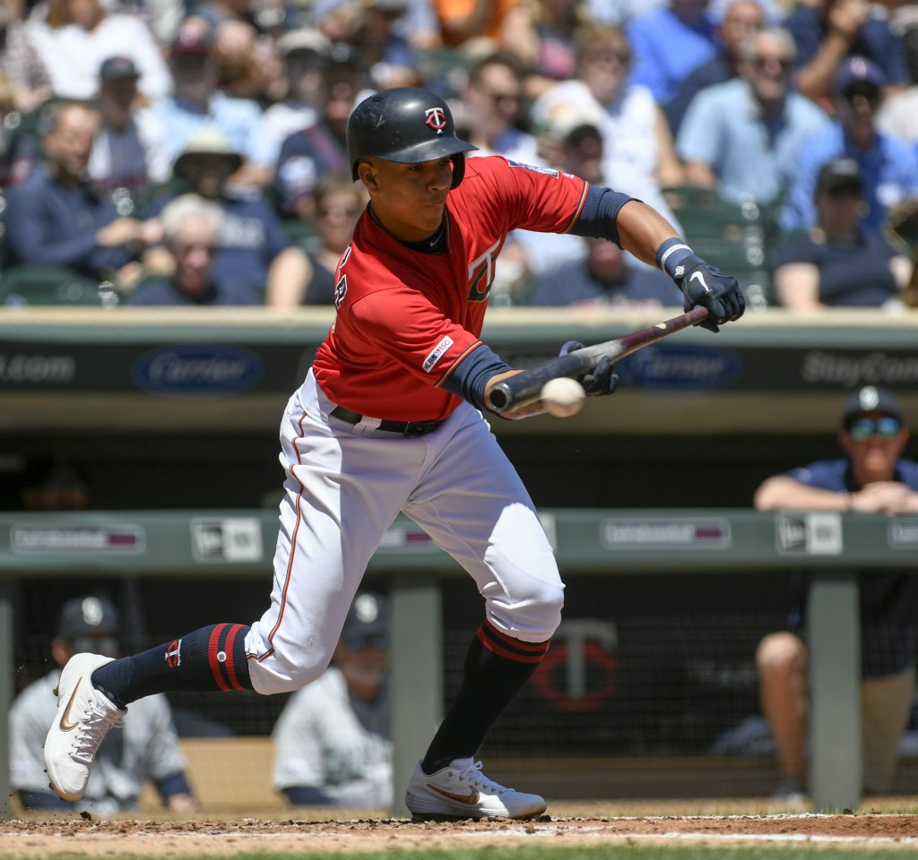 Minnesota Twins' Ehire Adrianza bunts for a single on a pitch by Seattle Mariners pitcher Yusei Kikuchi during in the second inning of a game Thursday