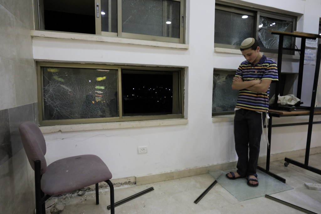 A student stands inside a Jewish religious school in Sderot, Israel, after it was hit by a rocket fired from the Gaza Strip, Thursday, June 13, 2019.