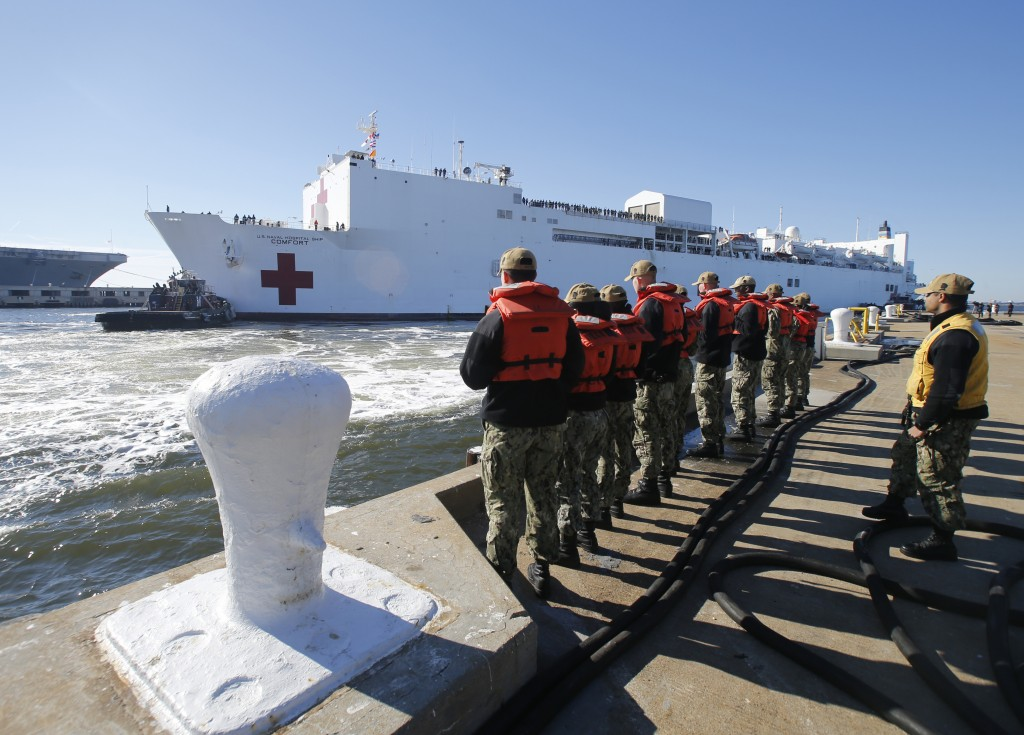 FILE - In this Dec. 18, 2018 file photo, line handlers wait as the US Navy Hospital Ship USNS Comfort arrives pier side at Naval Station Norfolk, in N
