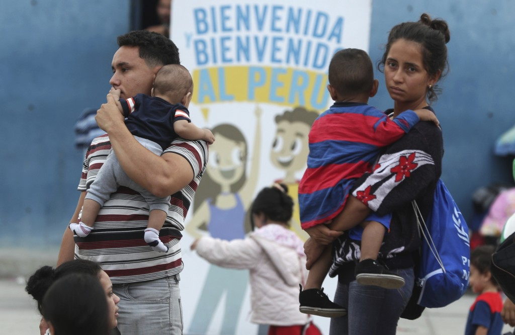 A couple of Venezuelan migrants arrive to migration controls in Tumbes, Peru, Friday, June 14, 2019. Venezuelan citizens are rushing to enter Peru bef