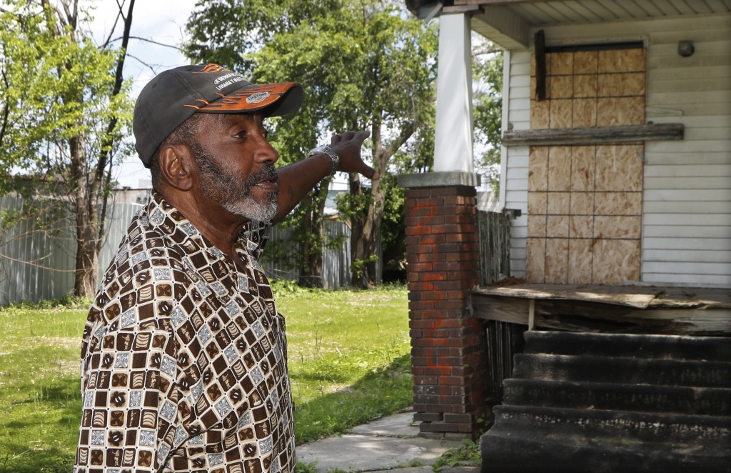 In a photo from Tuesday, June 11, 2019, Stanley Allen talks about an empty house next to his in Detroit. Hundreds of vacant houses in Detroit are bein
