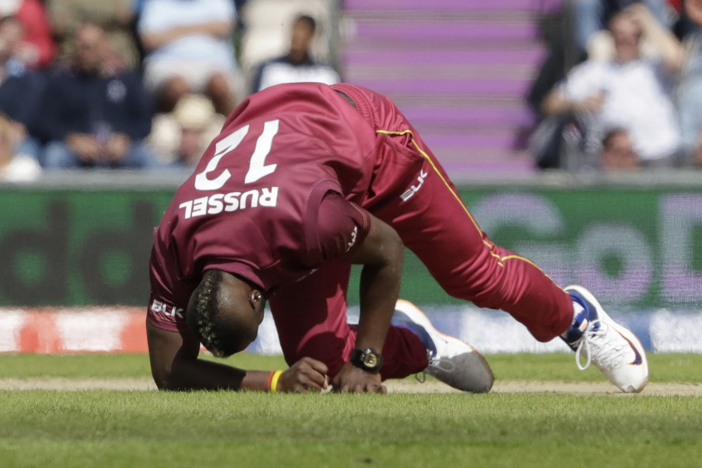 West Indies' Andre Russell gets up before walking off the field of play with an injury after bowling during the Cricket World Cup match between Englan...