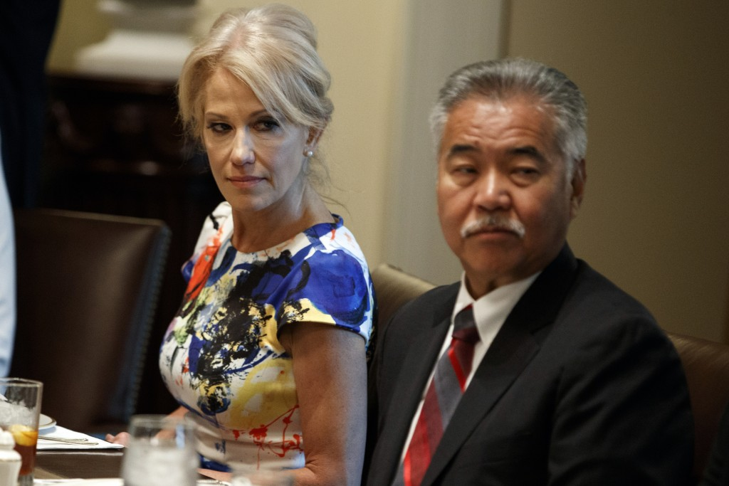 """White House counselor Kellyanne Conway, left, and Hawaii Gov. David Ige listen as President Donald Trump speaks during a meeting with governors on """"wo"""