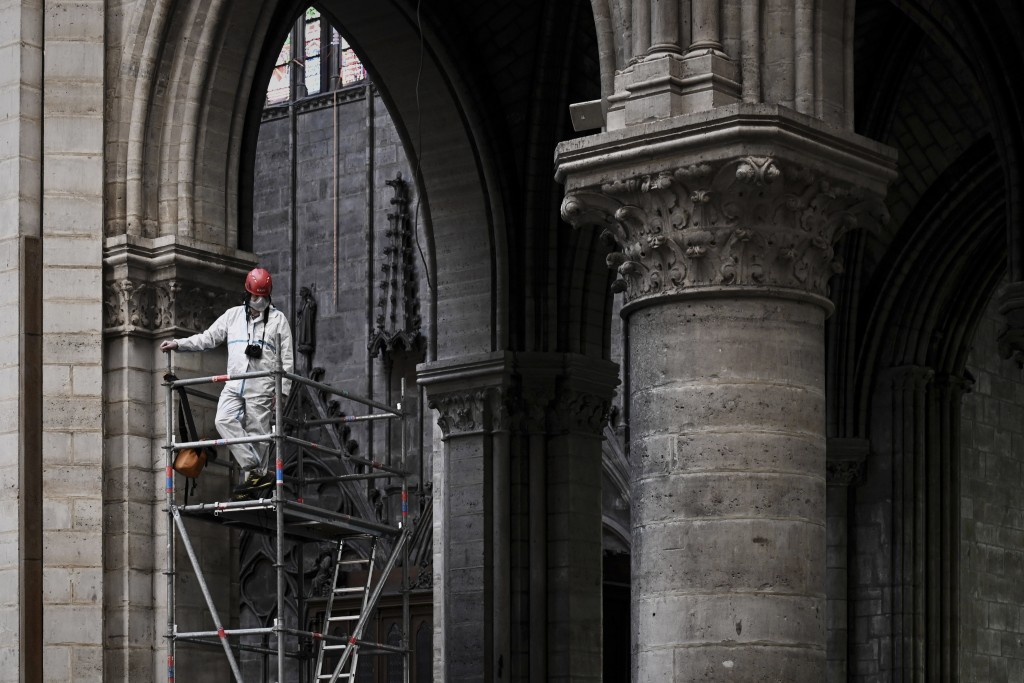 FILE - In this May 15, 2019 file photo, a worker stands on scaffolding during preliminary work inside the Notre Dame de Paris Cathedral, in Paris.  Th