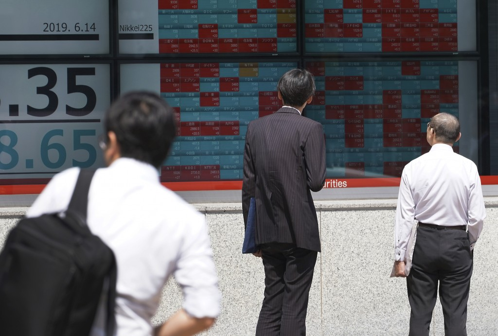 Pedestrians look at an electronic stock board showing Japan's Nikkei 225 index at a securities firm in Tokyo Friday, June 14, 2019. Asian shares were