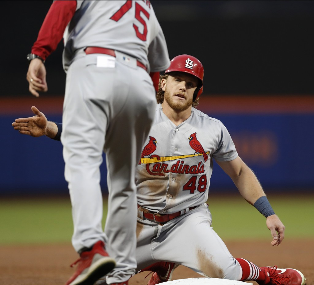 St. Louis Cardinals' third base coach Ron Warner congratulates Harrison Bader (48) after he stole third base during the third inning of a baseball gam...