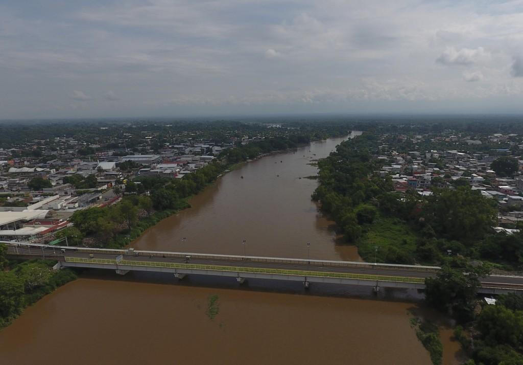 Vehicles drive across a border bridge linking Ciudad Hidalgo, Mexico, left, and Tecun Uman, Guatemala, over the Suchiate River, Thursday, June 13, 201