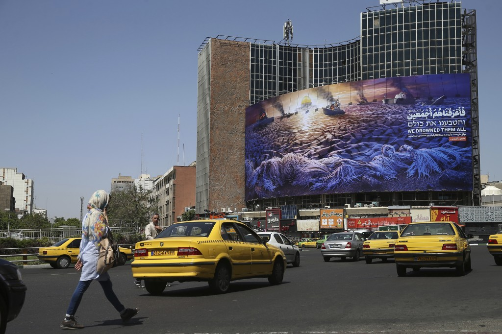 In this Wednesday, May 29, 2019 photo, People walk and vehicles drive at Vali-e-Asr Square in downtown Tehran where an anti-Israeli billboard is place
