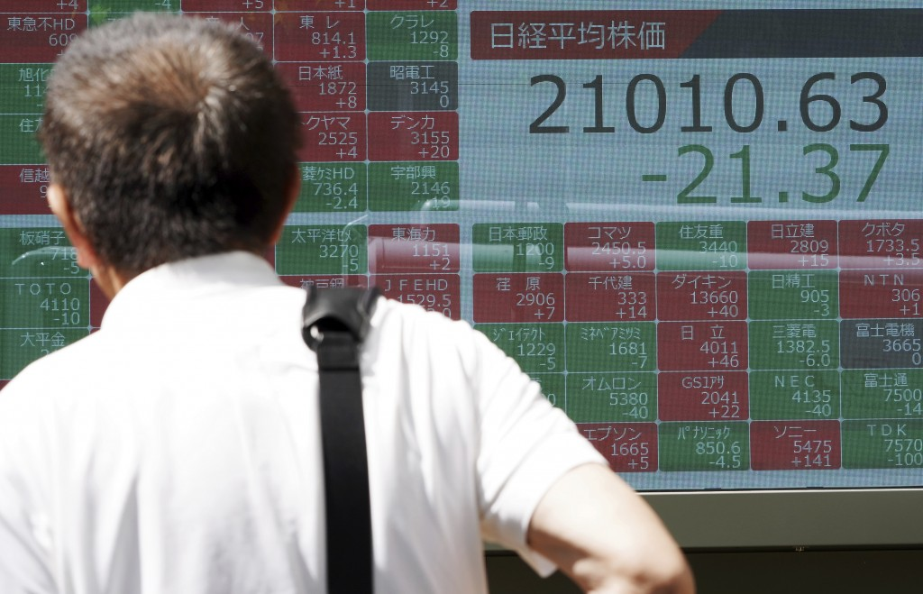 A man looks at an electronic stock board showing Japan's Nikkei 225 index at a securities firm in Tokyo Friday, June 14, 2019. Asian shares were mixed...