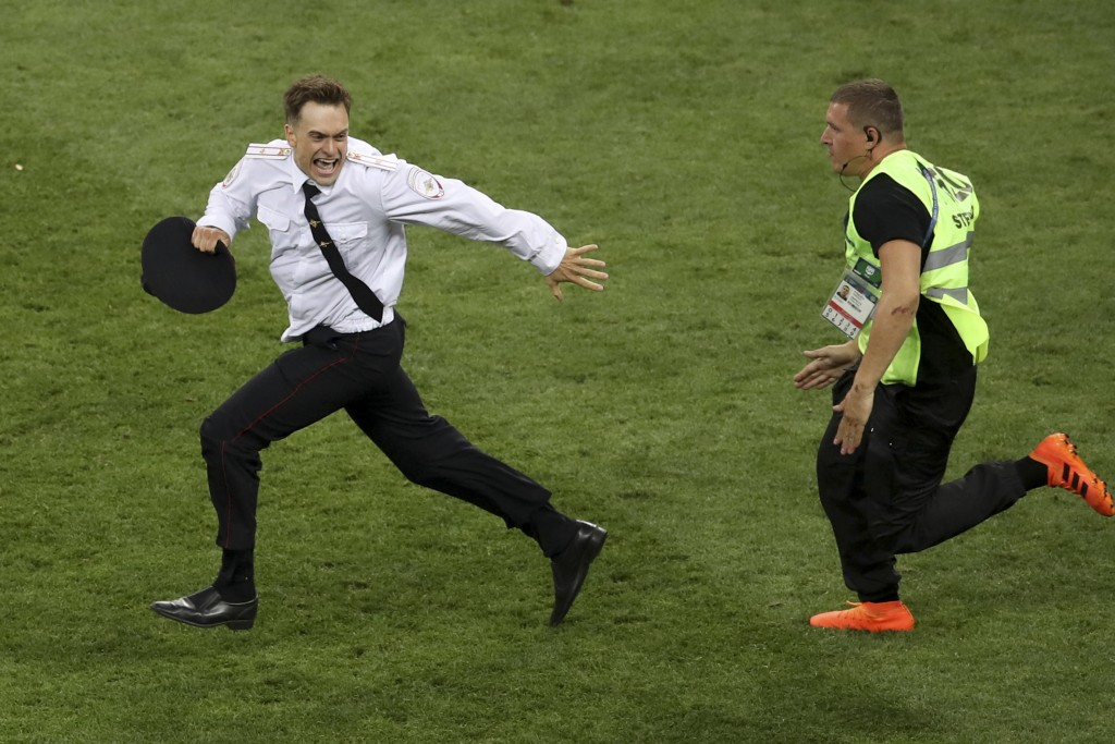 FILE - In this July 15, 2018 file photo, Pyotr Verzilov invading the pitch, runs away as a steward tries to stop him during the France and Croatia 201