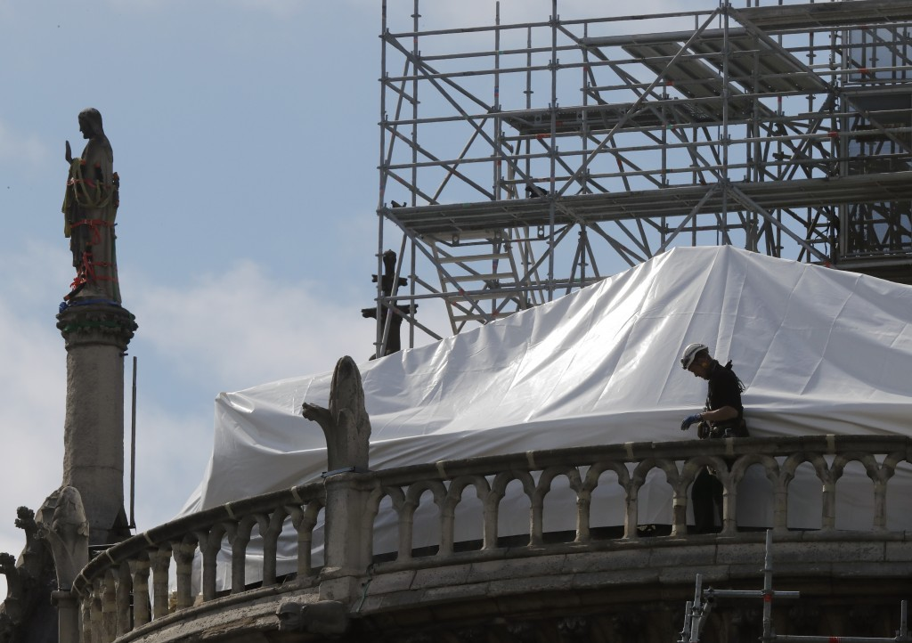 FILE - In this April 26, 2019 file photo, a worker checks the waterproof tarps on Notre Dame cathedral in Paris. The billionaire French donors that pu