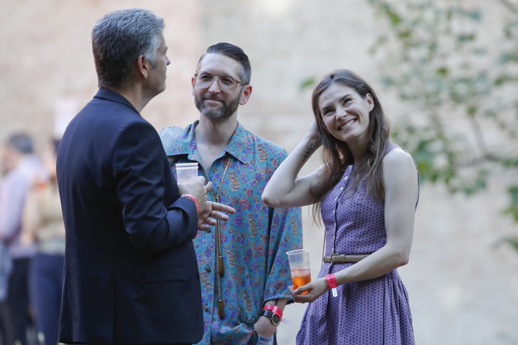 Amanda Knox, right, and her boyfriend Christopher Robinson, center, talk with a guest as they attend a cocktail for the opening of the Innocence Proje
