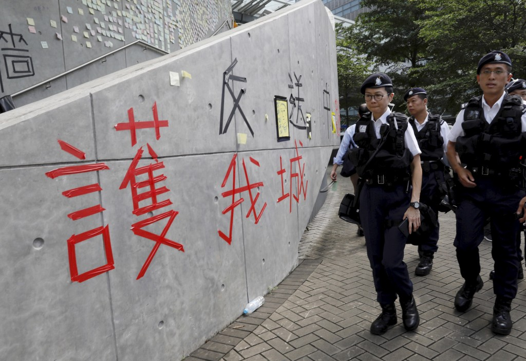 "Hong Kong police officers pass by words formed with tape which read ""Protect our city, against extradition to China"" near the Legislative Council in H"