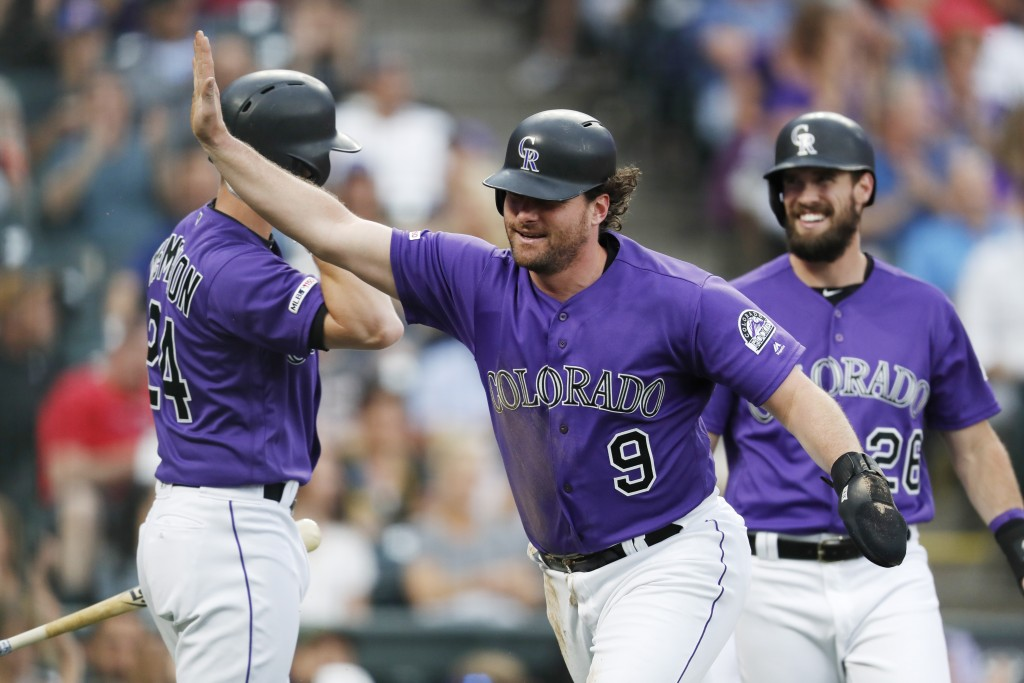 Colorado Rockies' Daniel Murphy, front, celebrates after scoring on a double by Ian Desmond, next to Ryan McMahon, back left, and David Dahl during th