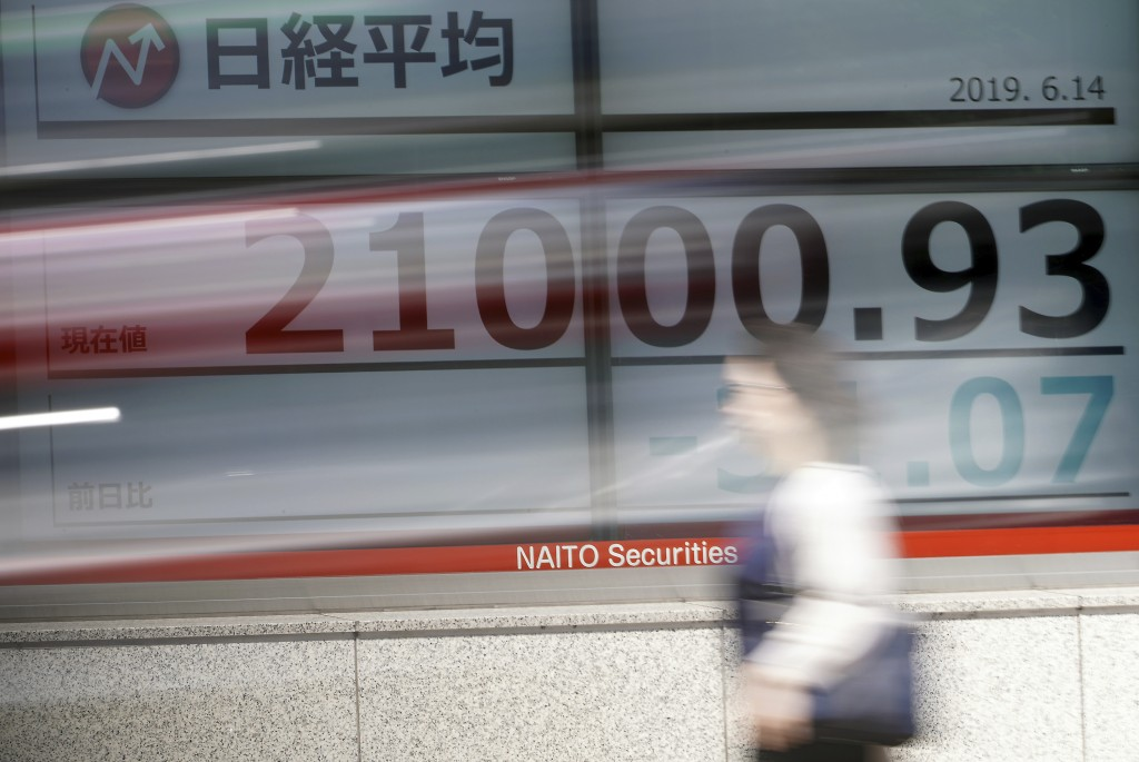 A woman walks past an electronic stock board showing Japan's Nikkei 225 index at a securities firm in Tokyo Friday, June 14, 2019. Asian shares were m...
