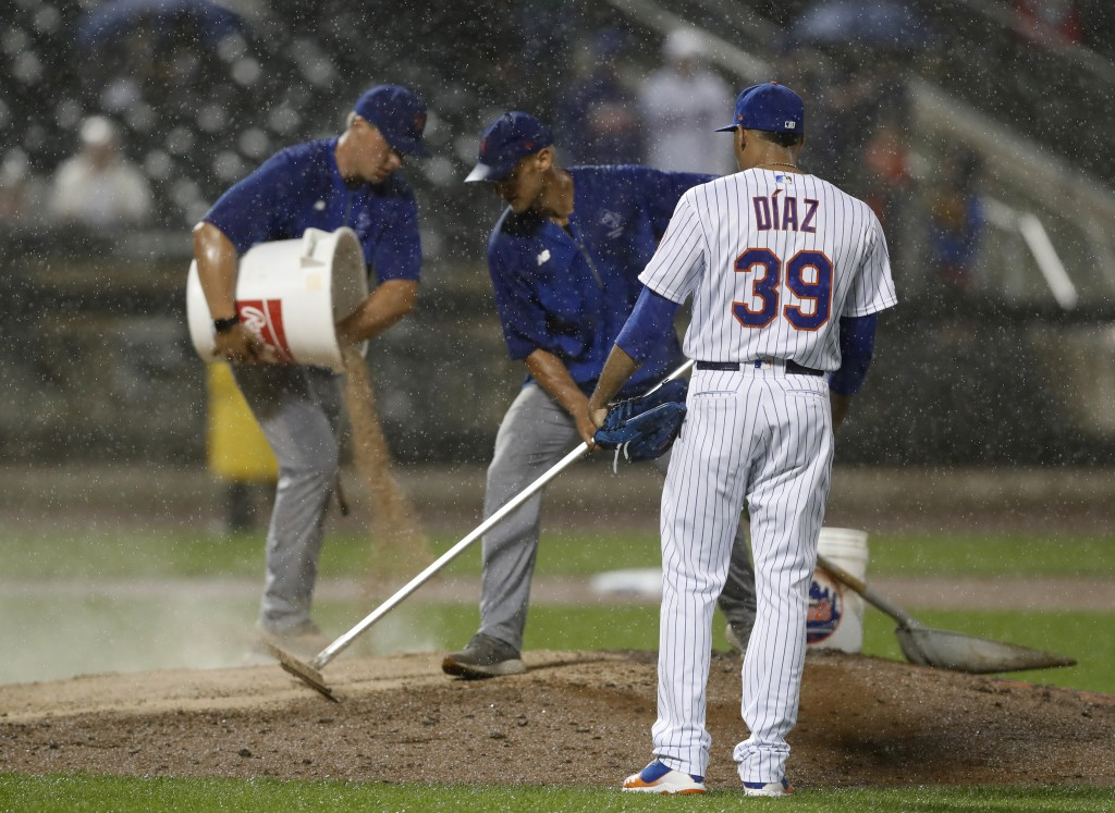 Heavy rain falls as New York Mets relief pitcher Edwin Diaz (39) watches groundskeepers groom the mound with extra dirt during the ninth inning of a b
