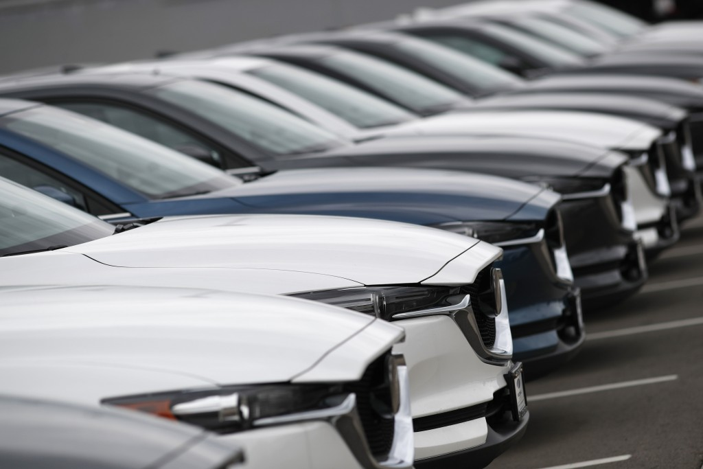 FILE- In this May 19, 2019, file photo, a line of unsold 2019 CX-5 sports-utility vehicles sits at a Mazda dealership in Littleton, Colo. On Friday, J