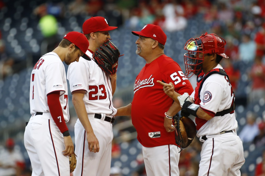 Washington Nationals starting pitcher Erick Fedde (23) speaks on the mound with shortstop Trea Turner, left, pitching coach Paul Menhart and catcher K...
