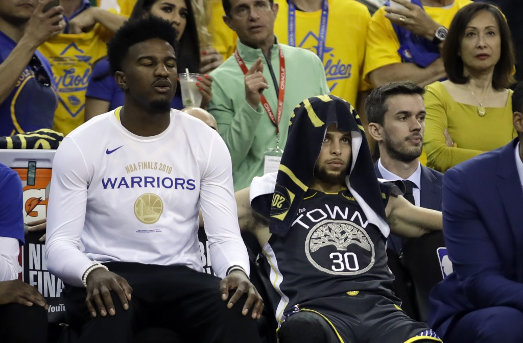 Golden State Warriors forward Jordan Bell, left, sits on the bench next to guard Stephen Curry (30) during the second half of Game 6 of basketball's N