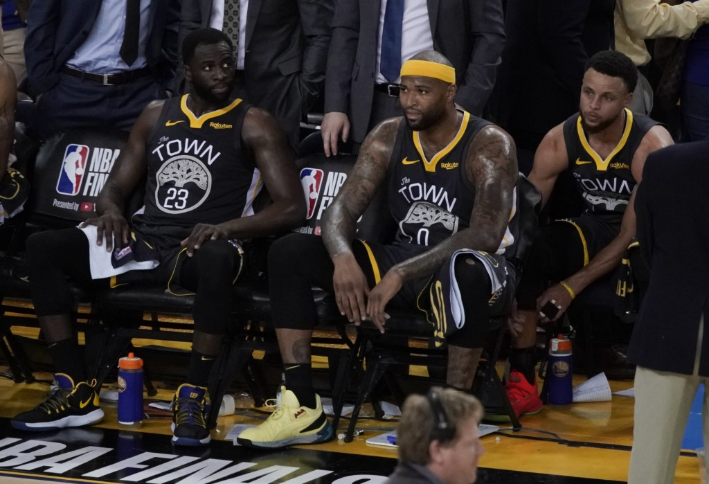 Golden State Warriors forward Draymond Green (23) sits on the bench next to center DeMarcus Cousins (0) and guard Stephen Curry (30) during the second