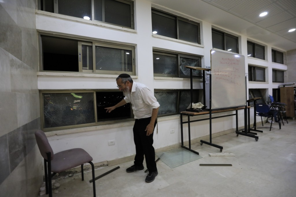 A rabbi stands inside a Jewish religious school in Sderot, Israel, after it was hit by a rocket fired from the Gaza Strip, Thursday, June 13, 2019. (A