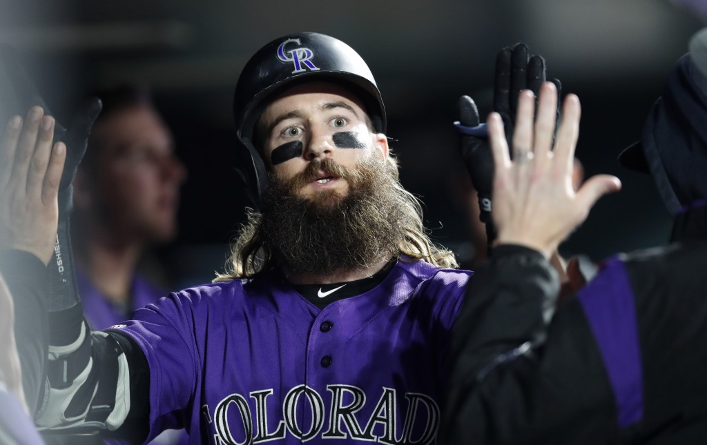 Colorado Rockies' Charlie Blackmon is congratulated by teammates as he returns to the dugout after hitting a solo home run off San Diego Padres relief