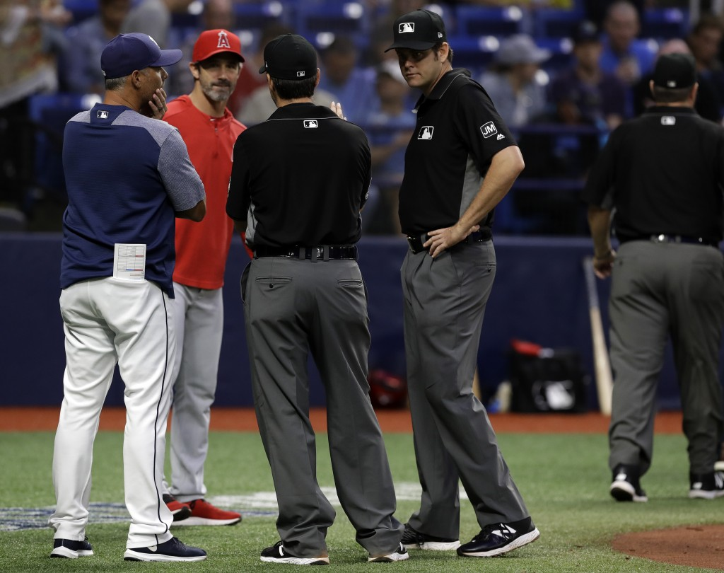 Tampa Bay Rays manager Kevin Cash. left, and Los Angeles Angels manager Brad Ausmus talk with the umpiring crew after a power failure at Tropicana Fie