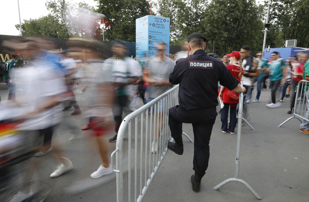 FILE - In this June 17, 2018, file photo, a Russian police officer controls an entrance ahead of the group F match between Germany and Mexico at the 2