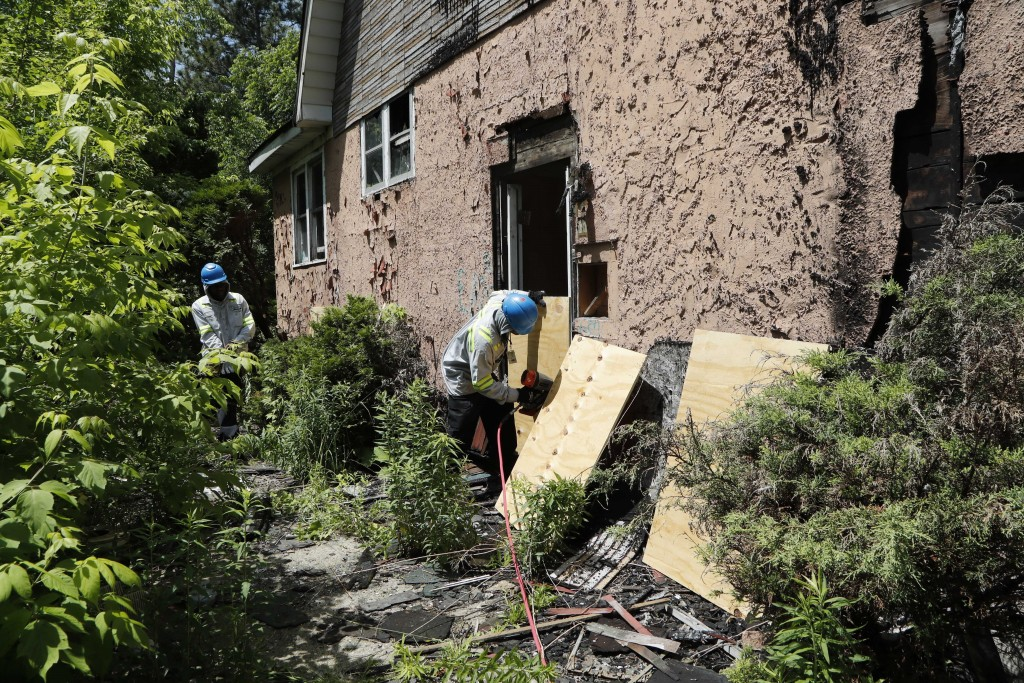 In a photo from Tuesday, June 11, 2019, members of the Detroit's Board Up Brigade board up a vacant home in north Detroit. Hundreds of vacant houses i