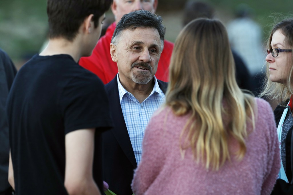 FILE - In this Friday, April 19, 2019, file photograph, Frank DeAngelis, center, greets well-wishers during a vigil at the memorial for victims of the