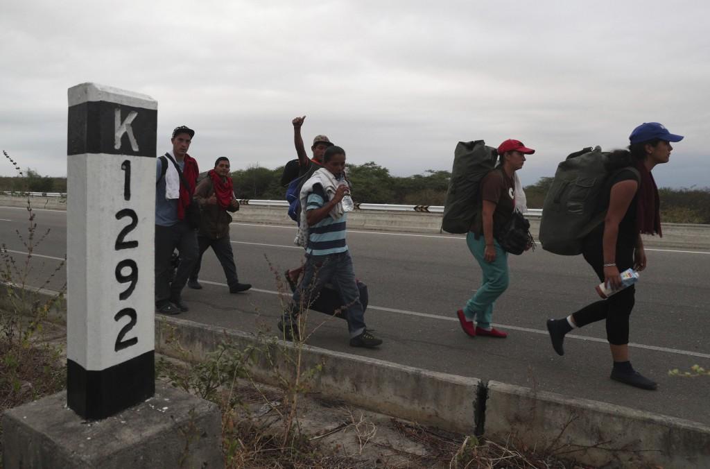 Venezuelan migrants walk on the Pan-American Highway, after crossing the border Peru - Ecuador border, in Tumbes, Peru, Friday, June 14, 2019. Venezue