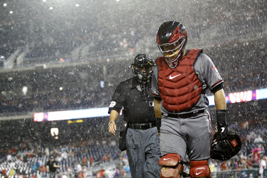 Arizona Diamondbacks catcher Alex Avila, right, and home plate umpire Alfonso Marquez walk off the field at the beginning of a rain delay in the eight...