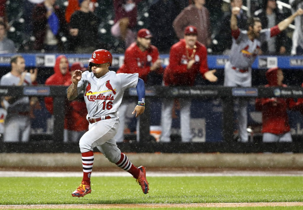St. Louis Cardinals react from the dugout as Cardinals' Kolten Wong hustles home on Harrison Bader's double during the ninth inning of a baseball game...