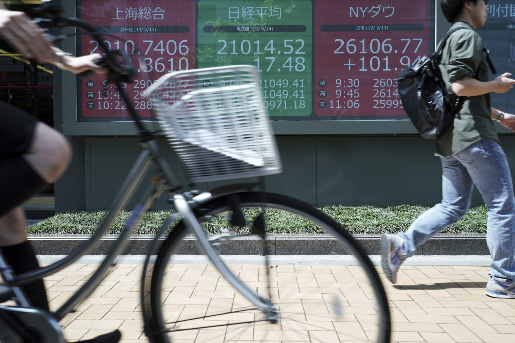 A man walks past an electronic stock board showing Japan's Nikkei 225 index at a securities firm in Tokyo Friday, June 14, 2019. Asian shares were mix...
