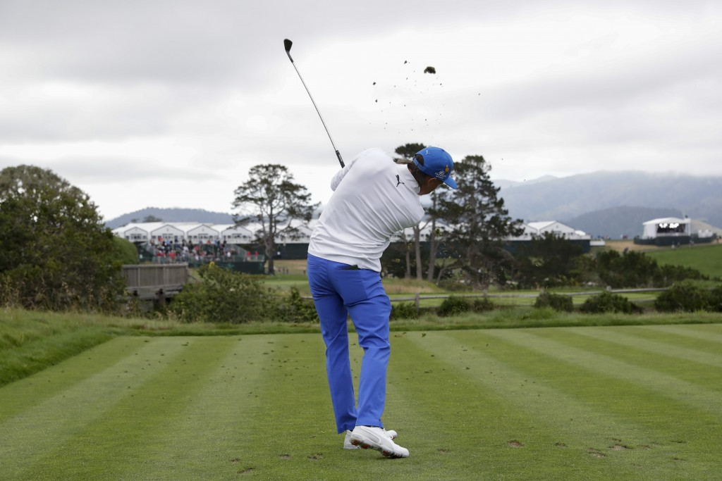 Rickie Fowler watches his tee shot on the fifth ho...