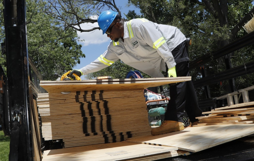 In a photo from Tuesday, June 11, 2019, Martis Wideman, a member of the Detroit's Board Up Brigade, cuts plywood to size in Detroit. Hundreds of vacan