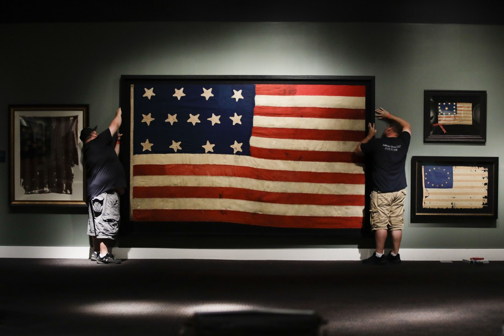 """In this Wednesday, June 12, 2019 photo, workmen hang a Federal Era flag as part of the new exhibit """"A New Constellation: A Collection of Historic 13-S"""
