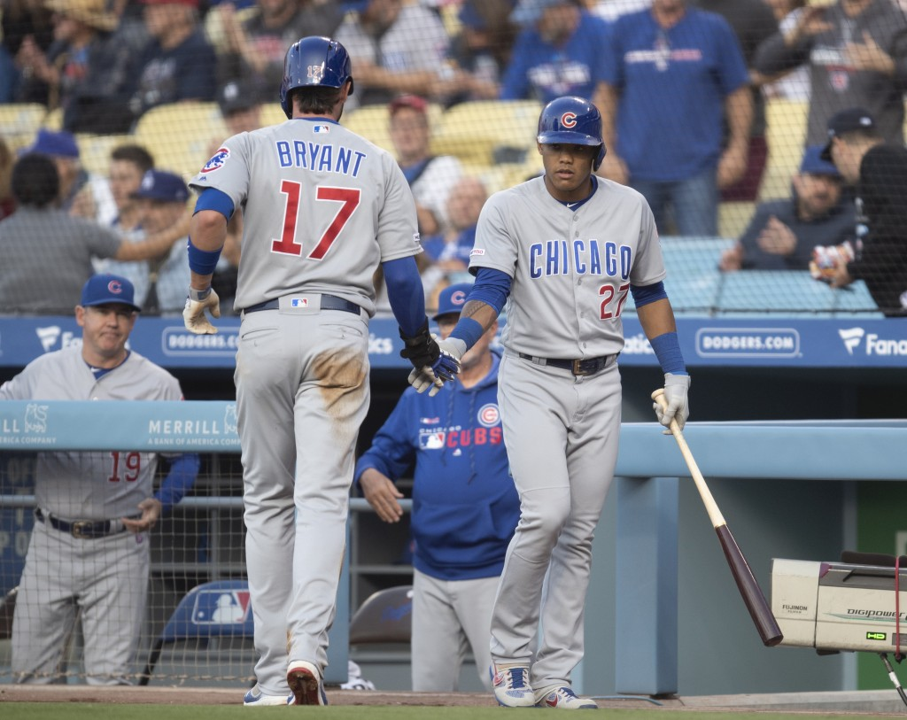 Chicago Cubs' Addison Russell, right greets Kris Bryant after Bryant scored against the Los Angeles Dodgers during the first inning of a baseball game