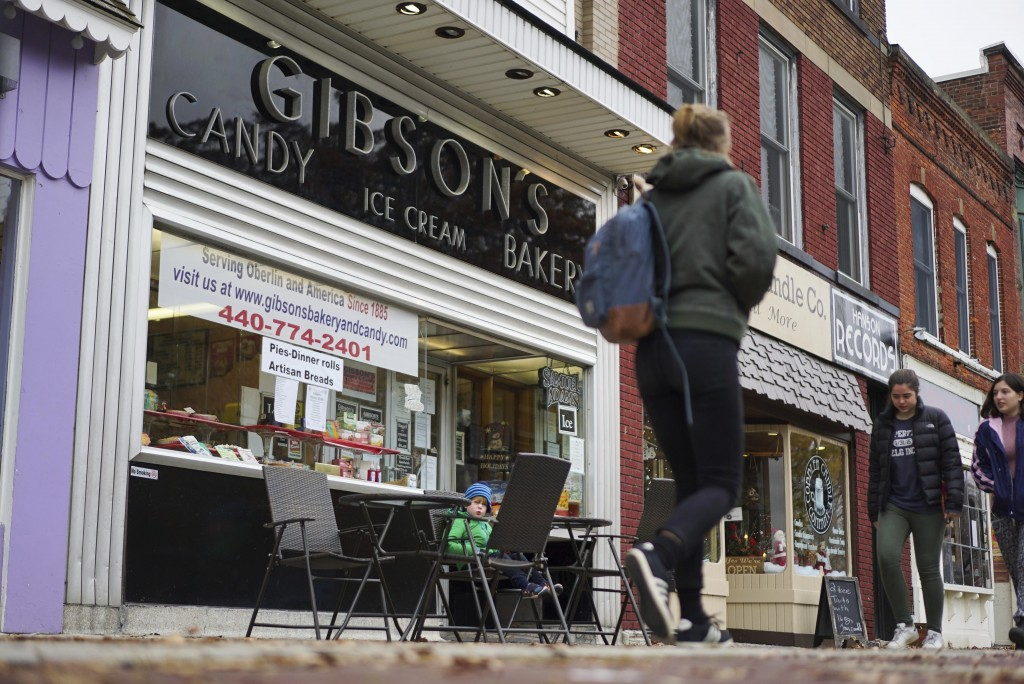FILE - In this Nov. 22, 2017 file photo, pedestrians pass the storefront of Gibson's Food Mart & Bakery in Oberlin, Ohio. A jury has awarded $11 milli...