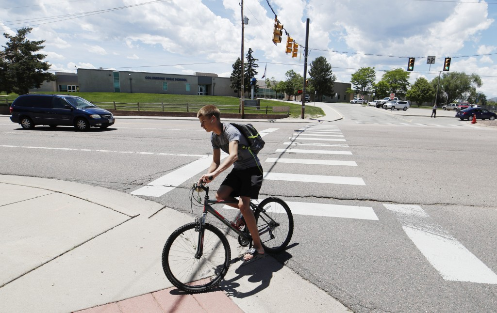 A bicyclist rides away from Columbine High School, Thursday, June 13, 2019, in Littleton, Colo. The school district is considering the demolition of C